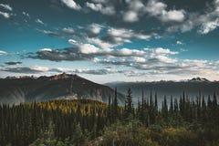 Opinión de la puesta del sol del soporte Revelstoke a través del bosque con el cielo azul y las nubes Lago Capilano foto de archivo