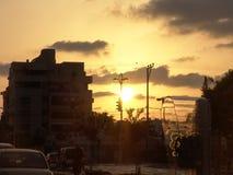 Opinión de la puesta del sol una cabina de teléfono de la calle de la ciudad, aparcamiento y la gente real en su manera imagen de archivo