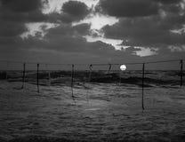 Opinión de la puesta del sol del verano de una playa debajo de un cielo nublado en blanco y negro, cuerda con las banderas que cu foto de archivo libre de regalías