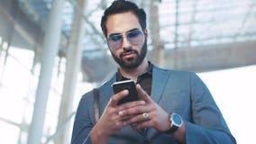 Opinión de la rotación un hombre acertado barbudo que usa su teléfono por la entrada del aeropuerto, resbalando la pantalla, mira metrajes
