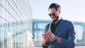 Opinión de la rotación un hombre barbudo elegante que hace una pausa el terminal de aeropuerto y que usa su teléfono, sonriendo e almacen de video