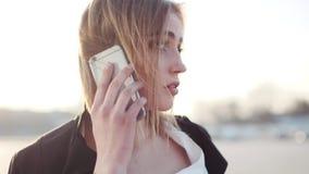 Opinión de la rotación una mujer rubia joven atractiva con maquillaje natural que habla en su teléfono Carrera acertada, moderna metrajes