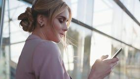 Opinión de la rotación una señora rubia elegante del negocio que usa su teléfono, mirando alrededor en una sol brillante moderno