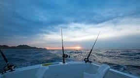 Opinión de la salida del sol de la caña de pescar en el barco de pesca de la carta en el lado pacífico de Cabo San Lucas en Baja  fotos de archivo