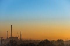 Opinión de la salida del sol con la fábrica del generador del poder y de calor Fotografía de archivo libre de regalías