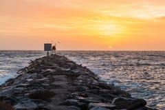 Opinión de la salida del sol mientras que en el embarcadero de la roca Foto de archivo