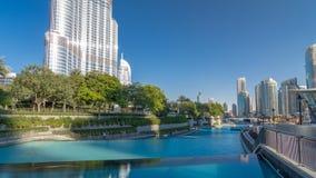 Opinión de la tarde de la cascada del agua cerca de las fuentes del baile en timelapse céntrico en Dubai, UAE metrajes