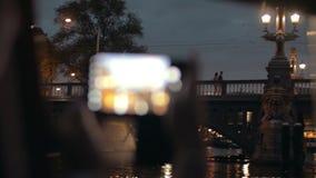 Opinión de la tarde del cierre encima de la mano de la mujer con el smartphone que toma la imagen de Blauwbrug, Amsterdam, Países metrajes