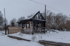 Opinión de la tarde sobre la pequeña casa de madera quemada en el bosque del invierno Fotos de archivo