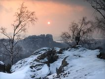 Opinión de la tarde a través de ramas del abedul, sobre quebrada a las rocas opuestas de la piedra arenisca y a la puesta del sol  Fotografía de archivo
