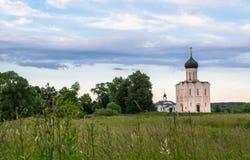 Opinión de la tarde a través del prado de Bogolubovo hacia la iglesia de la intercesión de la Virgen Santa en el río de Nerl Imagen de archivo libre de regalías