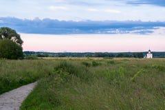 Opinión de la tarde a través del prado de Bogolubovo hacia la iglesia de la intercesión de la Virgen Santa en el río de Nerl Fotografía de archivo