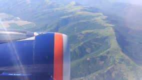 Opinión de la ventana del aeroplano que muestra el ala del vuelo plano sobre tierra almacen de metraje de vídeo