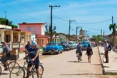 Opinión de la vida en las calles en la calle secundaria con la gente cubana y los coches clásicos americanos en el suburbio de Va imagen de archivo