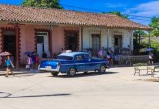 Opinión de la vida en las calles con un coche clásico americano azul en Santa Clara foto de archivo