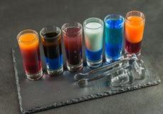 Opinión de lado izquierdo sobre seis diversas bebidas coloreadas del tiro, alineadas Imágenes de archivo libres de regalías