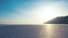 Opinión de perspectiva aérea de la superficie congelada nevada del lago Baikal desde arriba capturada con un abejón en Sunny W metrajes
