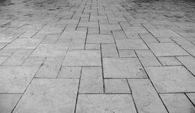 Opinión de perspectiva del Grunge monótono Gray Brick Marble Stone agrietado en la tierra para el camino de la calle Acera, calza Fotos de archivo libres de regalías