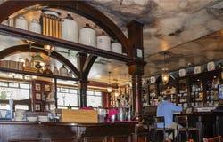Opinión de perspectiva dentro del Pub de Kilkenneys con el falso techo de mármol y la barra irlandesa vieja a lo lardo de una par Imagenes de archivo