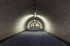 Opinión de perspectiva a través de un túnel Floodlighted oscuro Fotos de archivo