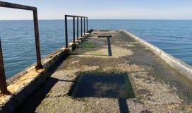 Opinión de perspectiva de un embarcadero viejo del cemento en la playa con el mar azul Fotos de archivo libres de regalías