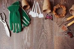 Opinión de sobremesa del jardinero de la primavera con las herramientas, los guantes, los potes de la turba y las etiquetas del j Fotos de archivo libres de regalías