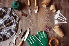 Opinión de sobremesa del jardinero de la primavera con las herramientas, los guantes, los potes de la turba y las etiquetas del j Fotos de archivo