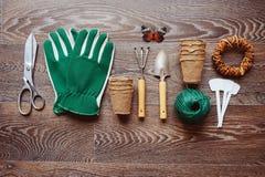 Opinión de sobremesa del jardinero de la primavera con las herramientas, los guantes, los potes de la turba y las etiquetas del j Fotografía de archivo libre de regalías