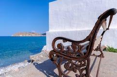 Opinión de Spinalonga de un banco en Plaka, Creta fotografía de archivo