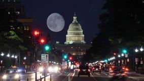 Opinión de Timelapse de la noche del tráfico de la avenida de Pennsylvania y de la bóveda del capitolio con la luna