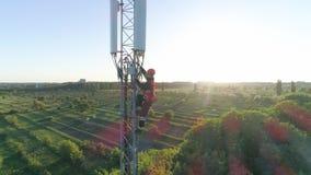 Opinión del abejón de la antena celular, torre de radio de la telecomunicación con el trabajador en paisaje hermoso de la ciudad  almacen de video