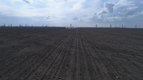 Opinión del abejón sobre el suelo marrón arado y el cielo hermoso, maquinaria agrícola en el arado del campo almacen de video