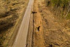 Opini?n del abej?n del trabajo de la reparaci?n de los camiones, de la niveladora y del camino en paisaje rural imagenes de archivo