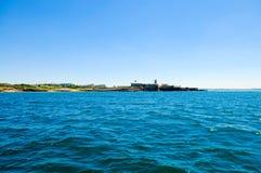 Opinión del agua - fortaleza en la playa de Carcavelos, cercanías de Lisboa, bandera portuguesa Foto de archivo