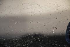 Opinión del camino a través de la ventanilla del coche con gotas de lluvia imagen de archivo libre de regalías