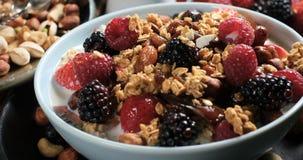 Opinión del carro de un desayuno de cereales con las bayas, las frutas secas y la leche almacen de video