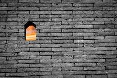 Opinión del cielo de la puesta del sol en pequeña ventana o agujero en ladrillo blanco y negro Fotos de archivo libres de regalías