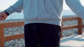 Opinión del detalle del cuerpo de la cuerda de salto del hombre en costa de mar en d3ia almacen de metraje de vídeo