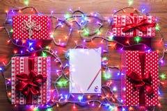 Opinión del escritorio desde arriba con la letra vacía a santa, a los presentes y a las luces de la Navidad, concepto retro de Na Fotografía de archivo libre de regalías