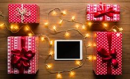 Opinión del escritorio desde arriba con la tableta, los presentes y las luces de la Navidad digitales Imagen de archivo