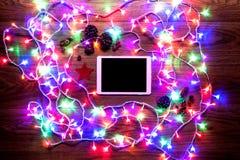 Opinión del escritorio desde arriba con las luces digitales de la tableta y de la Navidad, compras en línea de Navidad Imagenes de archivo