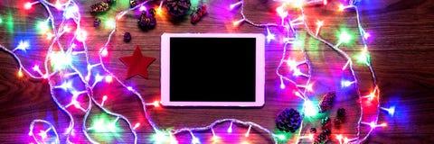 Opinión del escritorio desde arriba con las luces digitales de la tableta y de la Navidad, compras en línea de Navidad Fotos de archivo