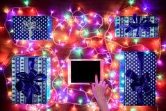 Opinión del escritorio desde arriba con las manos femeninas y la tableta digital, compras en línea de Navidad Imagen de archivo