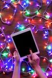 Opinión del escritorio desde arriba con las manos femeninas y la tableta digital, compras en línea de Navidad Fotografía de archivo libre de regalías