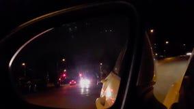 Opinión del espejo del lado del coche en la noche Vista posterior del vehículo del tráfico de la calle almacen de metraje de vídeo