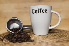 Opinión del frontal de la taza y del café y de los granos de café foto de archivo