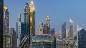 Opinión del horizonte de los edificios de Sheikh Zayed Road y del día de DIFC al timelapse de la noche en Dubai, UAE metrajes