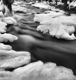 Opinión del invierno de la noche al arroyo congelado, a las ramitas heladas y a los cantos rodados helados sobre corriente rápida. Fotos de archivo libres de regalías