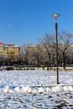 Opinión del invierno gente que camina en parque delante del palacio nacional de la cultura en Sofía, Bulga Foto de archivo