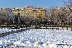 Opinión del invierno gente que camina en parque delante del palacio nacional de la cultura en Sofía, Bulga Imagen de archivo